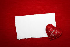 Red heart with an inscription and a white sheet of paper. On a red background Royalty Free Stock Images