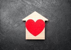 Red Heart inside a wooden house on a gray concrete background. The concept of a love nest, the search for new affordable housing royalty free stock images