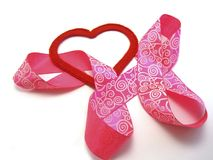 Red heart with a pink ribbon. Red heart intertwined with a pink ribbon stock photo