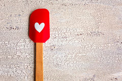 Red with heart kitchen spatula on wooden background Royalty Free Stock Photos