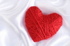 Red Heart of Knitting. Heart of Knitting on the satin background Stock Photo
