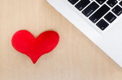 Red heart with laptop on wooden table, memory of love, heart sha. Ped with a laptop, blank keyboard Royalty Free Stock Photo