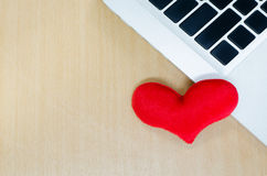 Red heart with laptop on wooden table, memory of love, heart sha. Ped with a laptop, blank keyboard Royalty Free Stock Photos