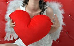 Red heart holding the angel girl clutching on a red background royalty free stock images