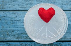 Red heart lies surrounded by the sharp cold of ice on a blue ta. The warm red heart lies surrounded by the sharp cold of ice on a blue table Royalty Free Stock Photos