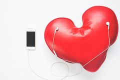 Red heart listening music from smartphone, Love concept on white. Background Stock Images