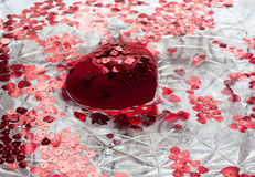 Red heart and little hearts in the water. A big red heart. Lots of little red hearts. They all float in water Royalty Free Stock Image