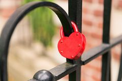 Red heart lock hanging on black cage. Close focus on empty red heart lock hanging on black cage meaning of forever love from lover Stock Photo