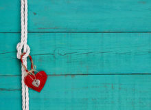 Red heart and lock hanging from rope knot border by antique blue wooden background