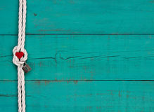 Red heart and lock hanging on white rope border against blue background