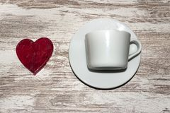 Red heart lollipop and a white cup and plate on rustic background royalty free stock images