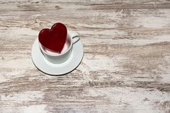 Red heart lollipop and a white cup and plate on rustic background stock image