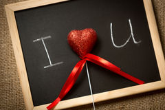 Red heart lying on blackboard with written declaration of love Stock Images