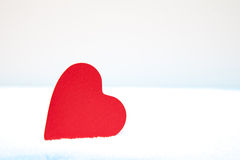 Red heart lying in snow Royalty Free Stock Photos