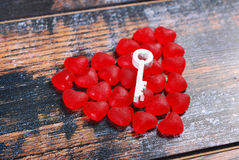 Red heart made of candies and a key on shabby background Royalty Free Stock Images