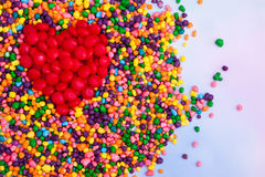 Red heart made of candy. Heart made of red candy surrounded with colorful candy Stock Image