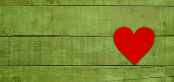 Red heart made of felt on green wooden background Royalty Free Stock Photography