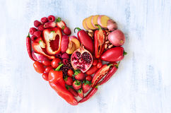 Red heart made from fresh raw fruits and vegetables. Collection of fresh red vegetables and fruits arranged in a heart shape on white rustic background Stock Photo