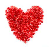 Red heart made from seeds of pomegranate,grenadine on white Royalty Free Stock Image