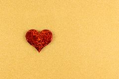 Red heart made of sparkles on gold background royalty free stock photo