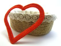 A gift from the heart. Red heart made of yarn next to basket on white background stock photos