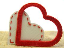 Two loving hearts. Red heart made of yarn and white paper heart together stock photo
