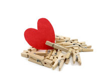 Red heart on many wooden pins. With one wooden pin pinch it on white background Stock Images