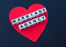 Red heart marriage agency. A large red heart shape  on a black background with text 'marriage agency' inscribed in black uppercase letters on small white cubes Stock Photos
