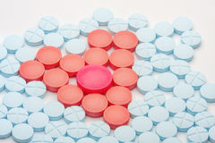 Red heart of medical tablets among blue pills Royalty Free Stock Images