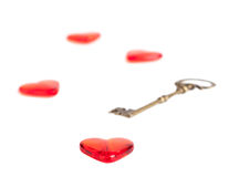 Red heart with a metal key on white. Royalty Free Stock Image