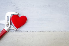 Red heart in metal pliers Stock Photos