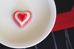 Red heart on the milk background. Concept Love. Red candy heart placed on the middle cup of milk on a printed background Royalty Free Stock Image