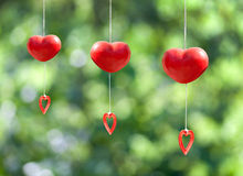red heart mobile hanging on green background Stock Photos