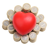 Red heart on money. Red heart on pile of coins with clipping path Royalty Free Stock Photo