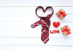 Red heart necktie and gift box with red ribbon and handmade crochet heart on wood background for happy fathers day royalty free stock photos