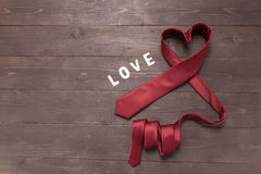 Red heart necktie is on wooden background Royalty Free Stock Images