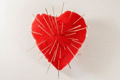 Red heart with needles in it on white background. And inscription, Concept of broken heart Royalty Free Stock Images