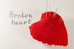 Red heart with needles in it on white background and inscription. Concept of broken heart Royalty Free Stock Images