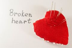 Red heart with needles in it on white background and inscription. Concept of broken heart Stock Photo
