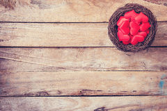 Red heart in the nest on wood background with space Royalty Free Stock Photography