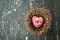 Red heart in nest on wooden background in country style. Stock Images