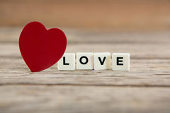 Red heart next to white blocks displaying love message Stock Photo
