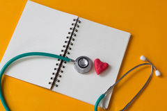 Red heart , notebook and a stethoscope Royalty Free Stock Images