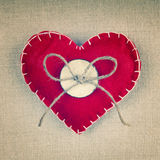 A red heart with an old wooden button and a bow made out of string Royalty Free Stock Images