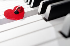 Red heart ornament with ladybug on piano keyboard Royalty Free Stock Photo