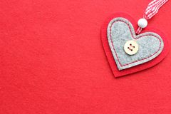 Red heart out of felt  on red background. Closeup. The concept of Valentine`s day Royalty Free Stock Image