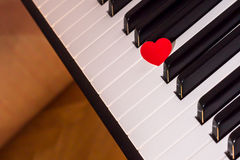 Red heart over piano keyboard Stock Images