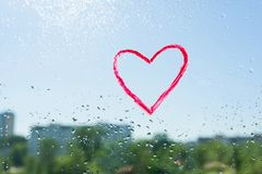 Red heart painted with lipstick on the window with water drops. Background blue sunny sky, drops shine in the sun. Red heart painted with lipstick on the window Royalty Free Stock Photo