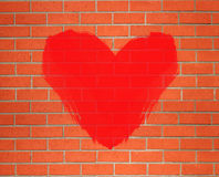 Red heart painted on orange brick wall background Royalty Free Stock Images