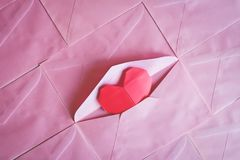Red heart paper origami in pink envelope background. For Valentine`s day concept, added colour filter effect stock photos